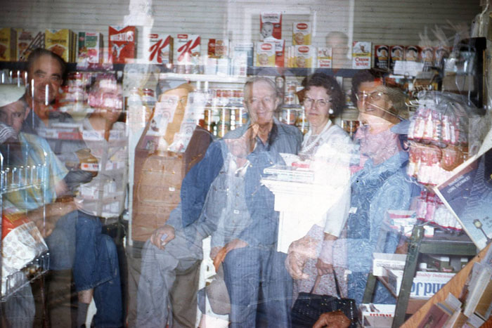 This haunting double-exposure photo, with its subjects fading from view, is the perfect end to our photo tour of the O.G. Evans General Merchandise store. From left are J. Rolland Post (seated in plaid shirt), Lloyd Poen (husband of photographer Eleanor Poen), two unidentified men, Delmar Brown (seated, with cap), Louie and Helen Reiber, Lizzie Evans, an unidentified man, and Harry Reiber (with cap and dark-framed glasses).