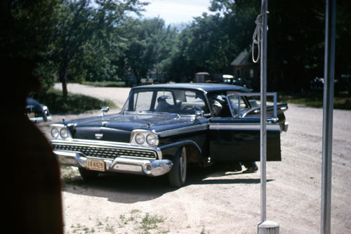 Car belonging to John H. Post, web editor's grandfather, is seen outside the store. Bill Moore's service station is across the street in the background.