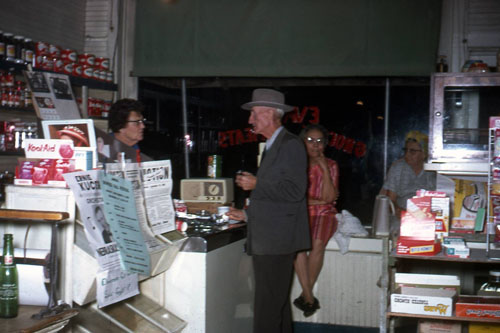 Lizzie Evans waits on customer Lester Woods. His wife, Catherine, is slightly to the right of him, sitting on a counter beneath the front windows. Lizzie's cousin Mattie Schnuerle is seen at far right.