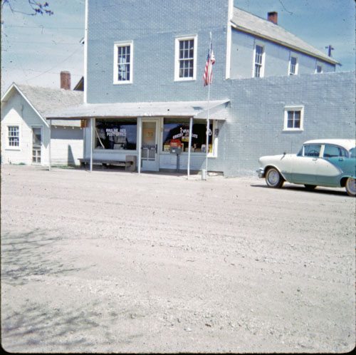 Exterior view of the O.G. Evans General Merchandise store. To the left of the store is the Sime Service Station.