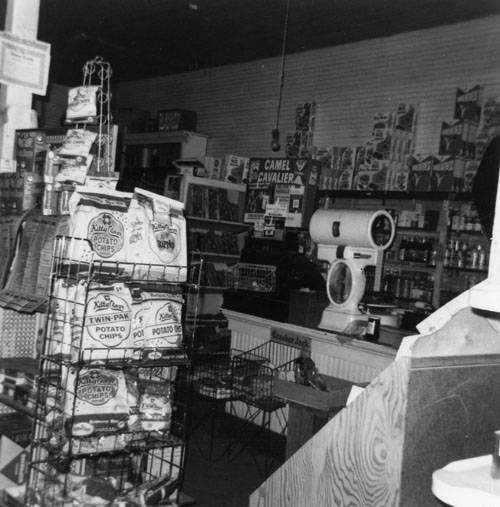 Another interior view of the store. The cash register is to the left of the white scales on the countertop.