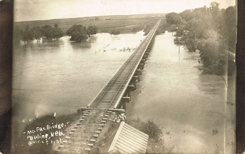The Missouri Pacific rail bridge is nearly inundated with water in this early 1900s photo. Pauline's east elevator can be seen in the distance, to the left of the tracks. Photo is from the Bennie Leighfield collection, courtesy of Doris Evans Alexander.