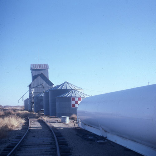 The Missouri Pacific railroad tracks lead to the original structure of Pauline's east elevator. Stockyards and a water tower once occupied the area behind the grain bins. This beautiful slide photo was taken Dec. 31, 1976 by area resident Dorothy Kosmacek.