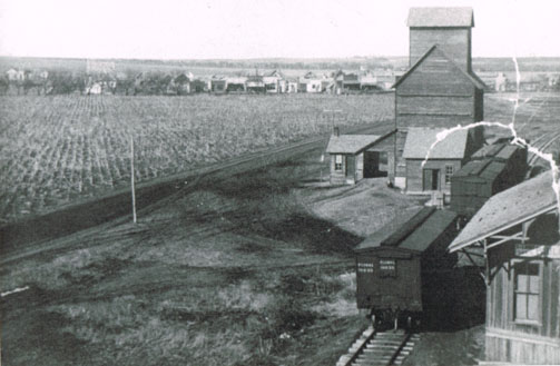 A panoramic view of Pauline's east elevator, with railroad cars and depot in lower right corner. In the distance can be seen Pauline's main street. The wood-frame schoolhouse is at the extreme left, dating this photo to before 1923. Photo is from the Bennie Leighfield collection, courtesy of Doris Evans Alexander.