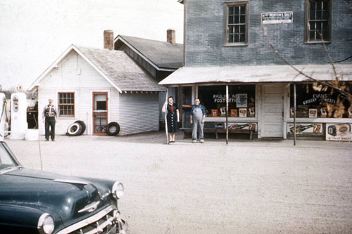 Sime service station is seen on the left, next to the O.G. Evans General Merchandise Store. Art Sime is pictured in front of his station, along with Lizzie and Owen Evans. Photo is from the Eleanor Thaden Poen collection, courtesy of Donna Knight.