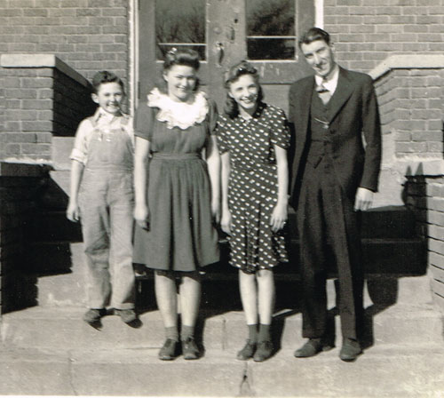 Freshman class. Left to right are Vern Bauder, Bonnie Moss, Norma Jean Kluver and Mr. Reynolds.